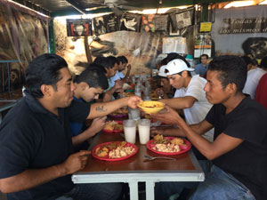 Recently deported immigrants share a meal.